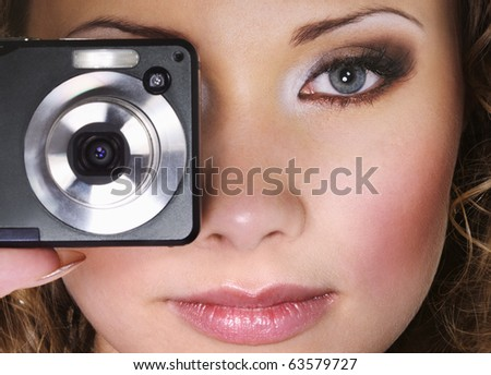Woman with digital photo camera. Focus on face.