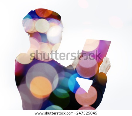 Woman with digital tablet composited with images of lights  - stock photo
