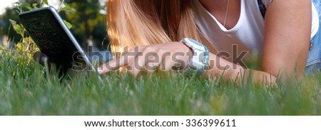 Woman with digital tablet in grass texting, a lot of copy space onblurred foreground - stock photo