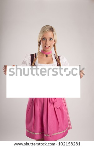 woman with dirndl holds empty signboard for advertising/woman with dirndl holds an empty signboard/girl in dirndl