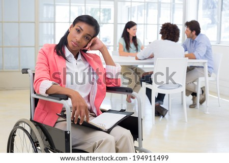 Woman with disability frowning with coworkers are in background in the office - stock photo