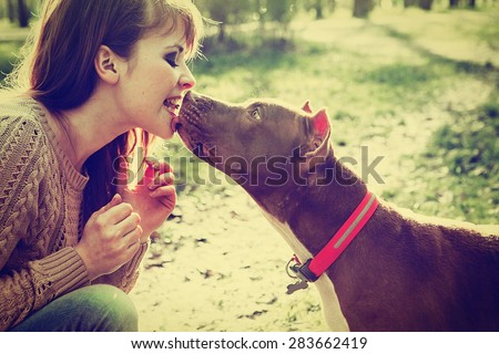 Woman with dog in park walking and playing - stock photo