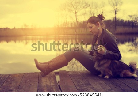 Woman with dog in sunset