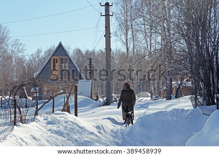 Woman with dog in winter village