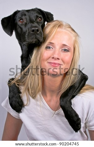 Woman with dog over her shoulder smiling - stock photo