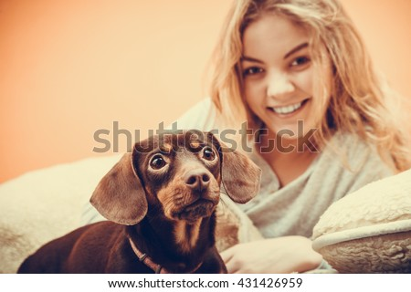 Woman with dog waking up in bed in the morning after sleeping. Young girl laying under wool blanket. Instagram filtered.
