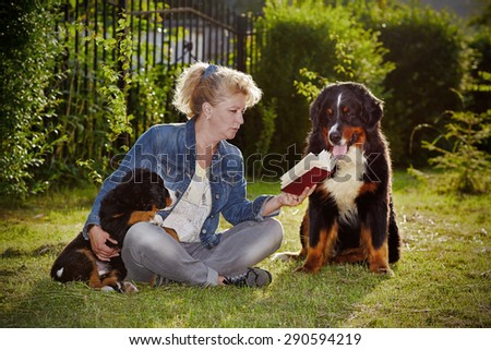 woman with dogs reading book in park - stock photo