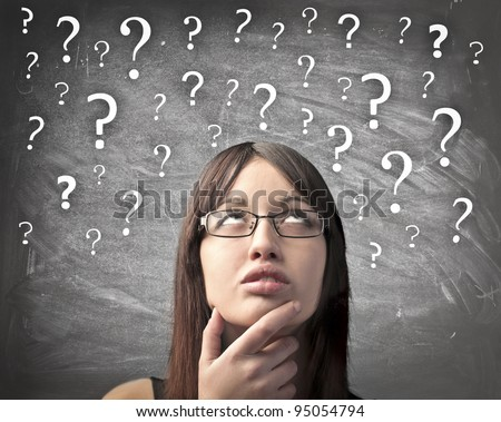 Woman with doubtful expression and question marks all over her head - stock photo