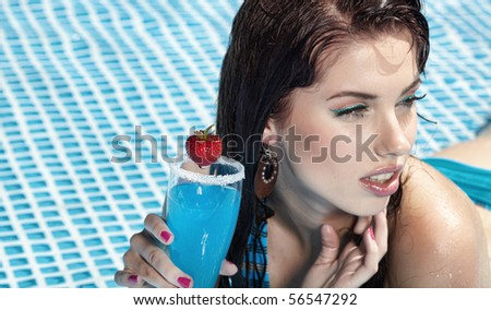Woman with drink  in swimming pool - stock photo