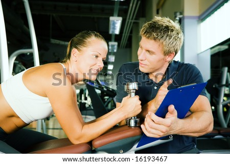 Woman with dumbbells in a gym, her personal trainer gives a report on her training - stock photo