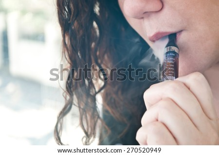 woman with e-cigarette on rust background - stock photo
