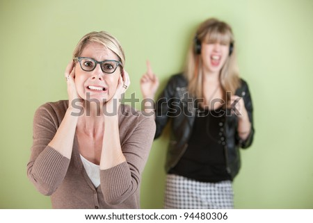 Woman with ears covered in front of loud teen - stock photo