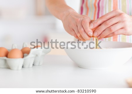 Woman with eggs in a kitchen - stock photo