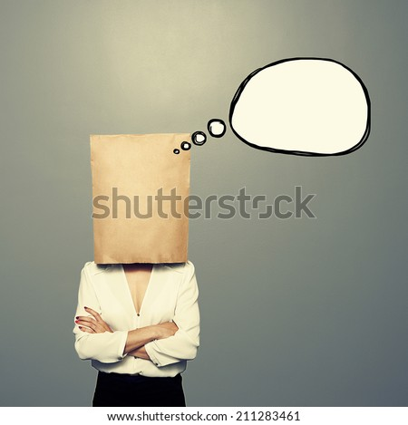 woman with empty paper bag on the head and drawing speech balloon over dark background - stock photo