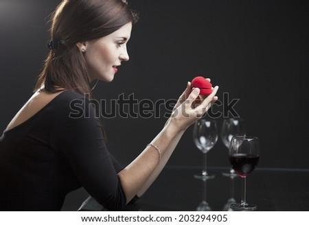 Woman with engagement ring in elegant restaurant - stock photo