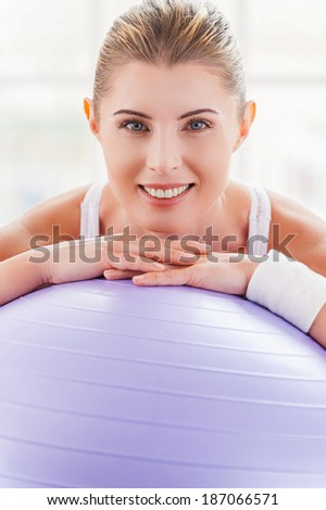 Woman with exercise ball. Beautiful mature woman leaning at fitness ball and smiling - stock photo