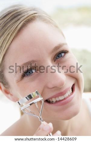 Woman with eyelash curler smiling - stock photo