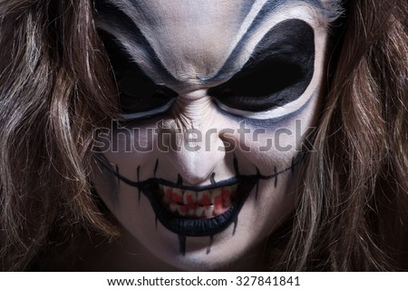Woman with face painting in dark room - stock photo
