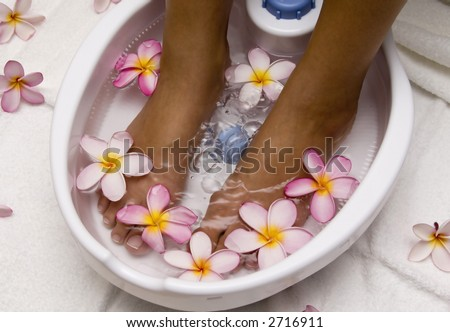 Woman with feet in a foot bath filled with water and flowers - stock photo