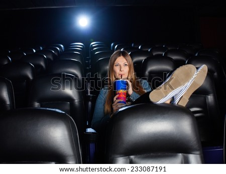 Woman with feetup on seat drinking cola while watching movie at cinema theater - stock photo