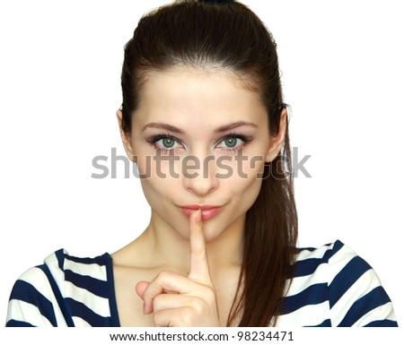 Woman with finger at mouth showing silence sign isolated on white background. Closeup portrait of beautiful green eyes girl. - stock photo
