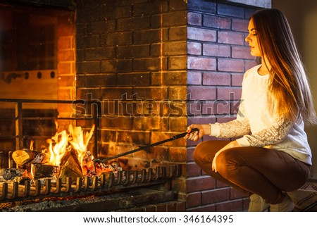 Woman with fire iron poker at fireplace. Young girl heating warming up and relaxing. Winter at home. - stock photo