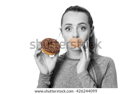 woman with first aid plaster over mouth unable to eat a donut
