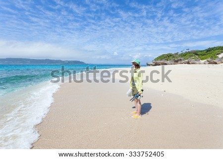 Woman with fishing gear standing on a deserted tropical island beach, Okinawa, Japan - stock photo
