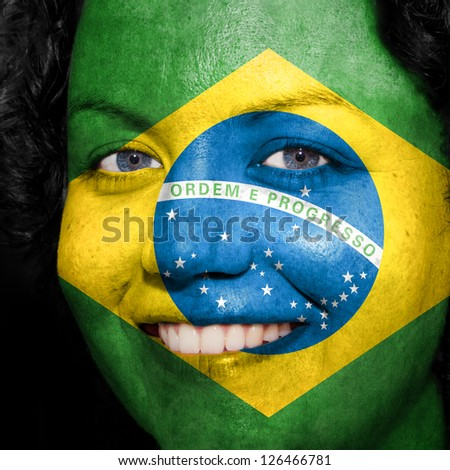 Woman with flag painted on her face to show Brazil support in sports - stock photo