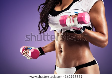 Woman with flat and sexy stomach working out with a dumbbell - stock photo