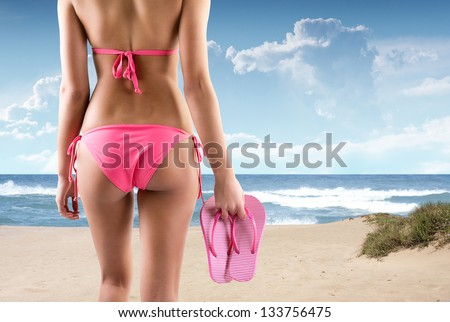 woman with flip flops on a beach - stock photo