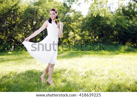 woman with flowers in a white dress walks in the park