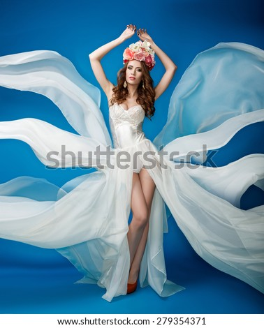 Woman with flowers on her head in a white dress on a blue background - stock photo