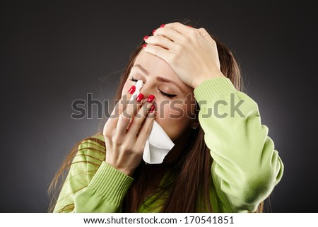 Woman with flu holding a tissue at her nose and her forehead, in pain - stock photo