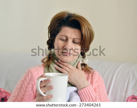 woman with flu symptoms holding a cup in his hand
