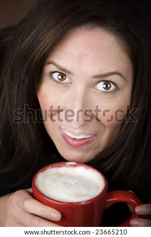 Woman with foam from coffee specialty drink on her lip and nose - stock photo