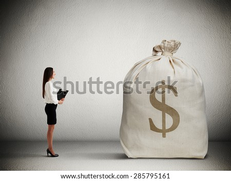 woman with folder standing in dark room and looking at big money bag - stock photo