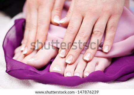 Woman with French manicured finger and toe nails displaying them for the viewer after enjoying a relaxing manicure in a beauty salon - stock photo