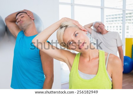 Woman with friends doing neck exercise in fitness club - stock photo