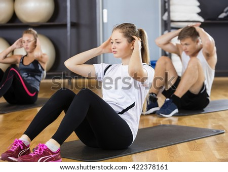 Woman With Friends Doing Situps In Gym - stock photo