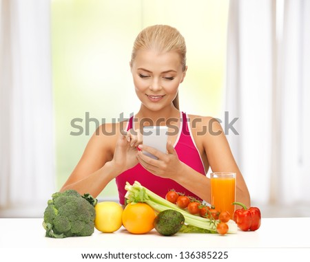 woman with fruits and vegetables counting calories on smartphone - stock photo
