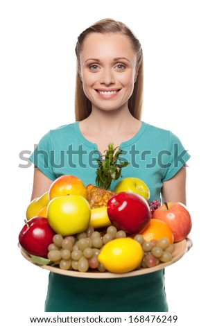 Woman with fruits. Beautiful young woman holding a plate with fruits and smiling while standing isolated on white