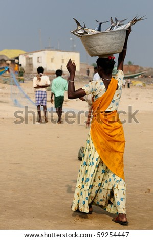 Woman with full dish crab on the head on a beach in Orissa, India