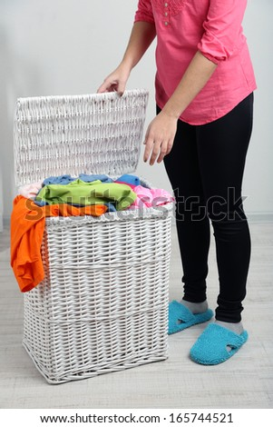 Woman with full laundry basket on gray background
