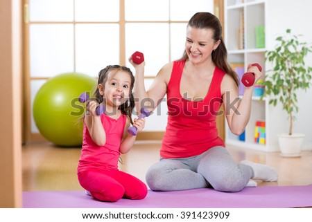 Woman with funny child do exercise lifting dumbbells
