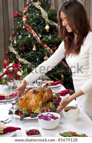 Woman with Garnished Christmas roasted turkey to celebrate traditional family dinner with salad, fruits, vegetables, wine and champagne glasses on Christmas tree background - stock photo