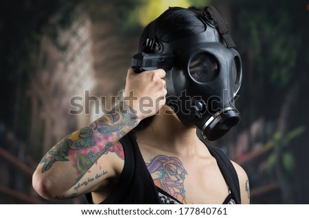 Woman with gas mask and gun in a grunge background - stock photo