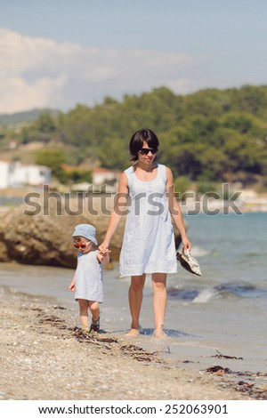 woman with girl walking along seashore