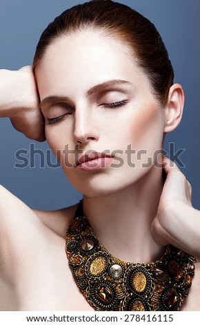 Woman with glamorous bronze jewelry - stock photo