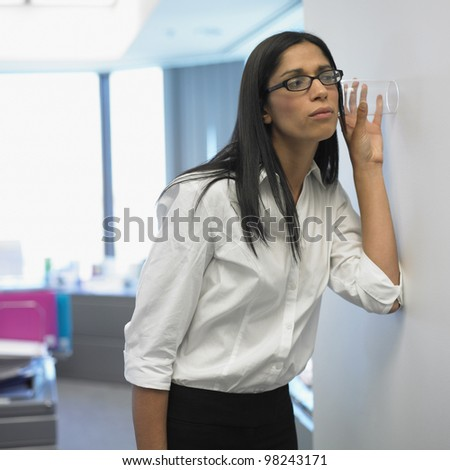 Woman with glass listening through wall in office - stock photo